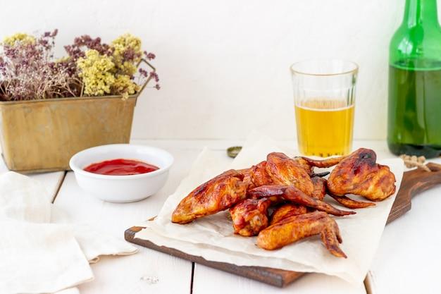 Ailes de poulet grillées avec de la bière et de la sauce rouge sur un fond en bois. snack à la bière. barbecue. recettes.