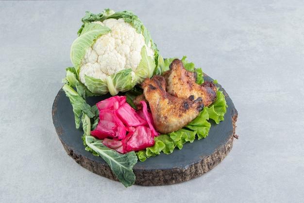 Ailes de poulet grillées et chou-fleur sur morceau de bois.