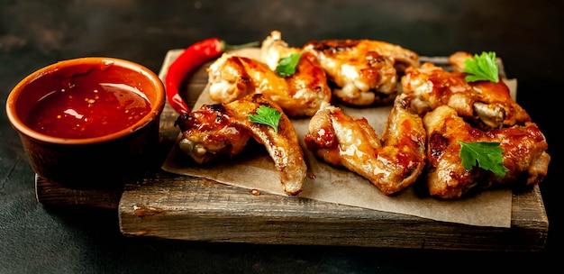 Ailes de poulet grillées dans une sauce barbecue au persil sur une planche à découper sur une table en béton. vue de dessus.