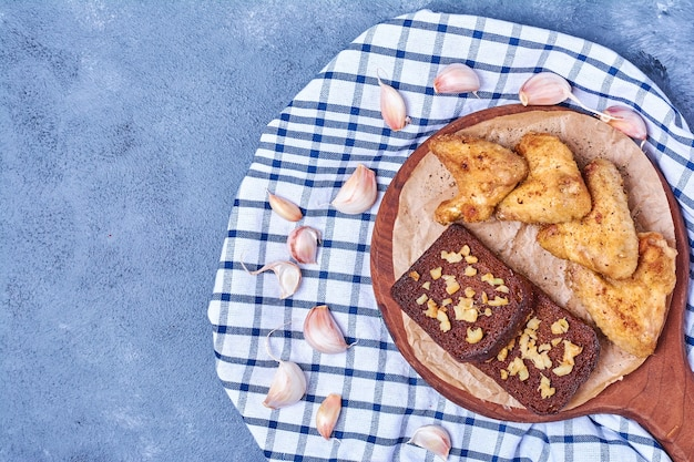 Ailes de poulet grillées avec du pain noir sur une planche de bois sur bleu