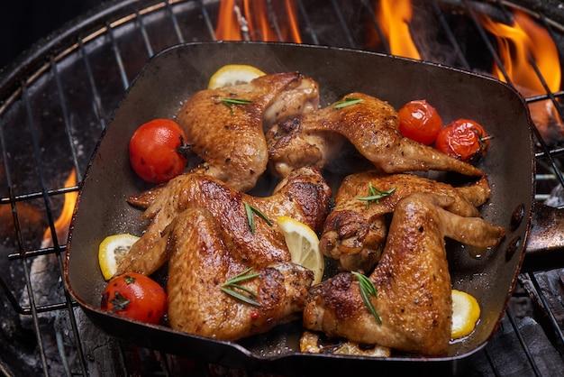 Ailes de poulet grillées sur le gril flamboyant avec légumes grillés à la sauce barbecue avec graines de poivre romarin, sel.