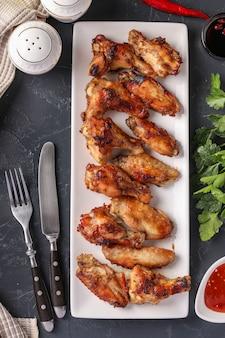 Ailes de poulet grillées sur plaque blanche et sauce tomate sur noir