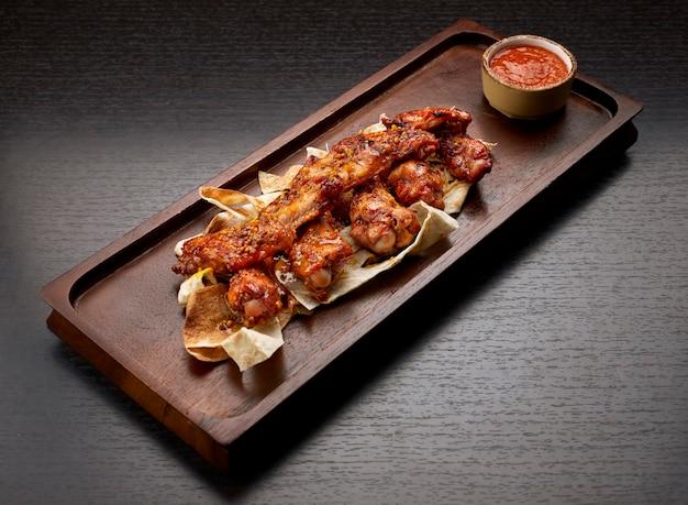 Ailes de poulet grillées en sauce, avec du ketchup, sur une planche de bois, sur un fond sombre