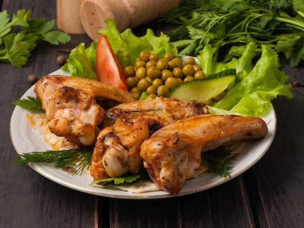 Ailes de poulet grillées savoureuses décorées de légumes