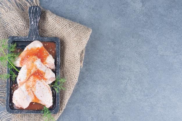 Ailes de poulet marinées avec sauce sur tableau noir.