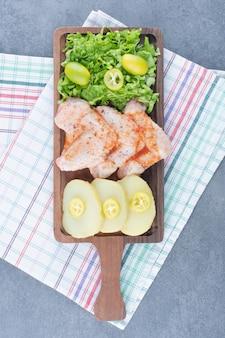 Ailes de poulet marinées et verts sur planche de bois.