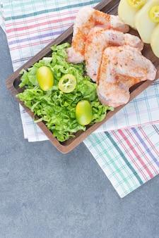 Ailes de poulet marinées et verts sur plaque en bois.