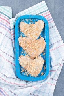 Ailes de poulet non cuites avec chapelure sur plaque bleue.