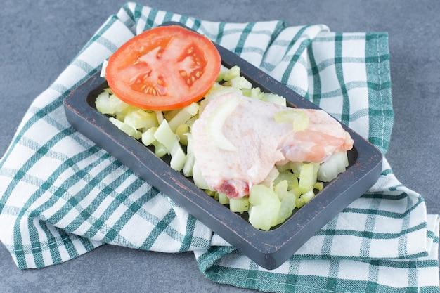 Ailes de poulet non cuites et tomate sur plaque noire.
