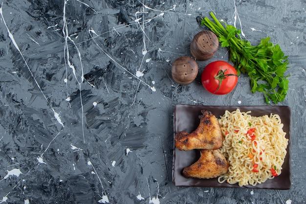 Ailes de poulet et nouilles sur un plateau à côté de légumes, sur le fond de marbre.