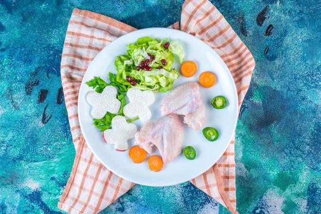 Ailes de poulet, persil, carotte et poivre sur une assiette sur le torchon