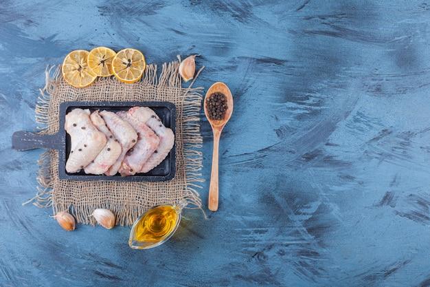 Ailes de poulet sur une planche sur une serviette en toile de jute à côté d'un bol d'huile, d'épices, d'une cuillère et de citron séché sur la surface bleue