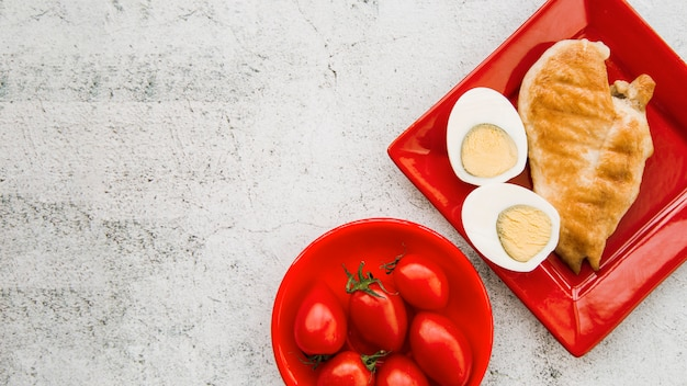Ailes de poulet rôties avec œuf à la coque et tomate sur fond rugueux