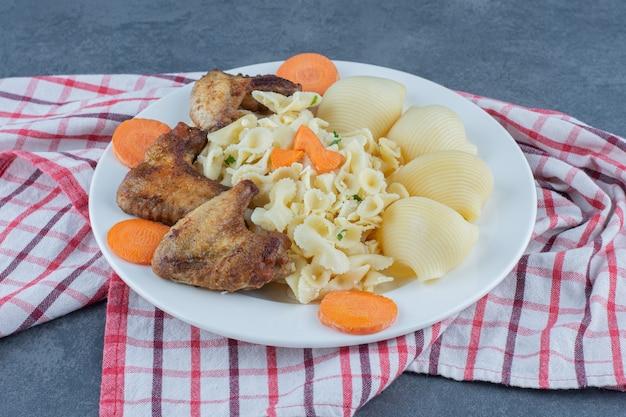Ailes de poulet rôties et pâtes sur plaque blanche.