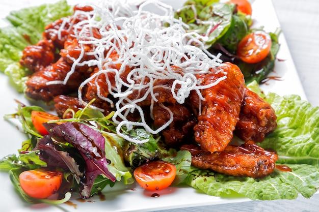 Ailes de poulet avec sauce barbecue, salade, tomates et chips sur une plaque blanche