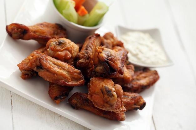 Ailes de poulet avec sauce et légumes