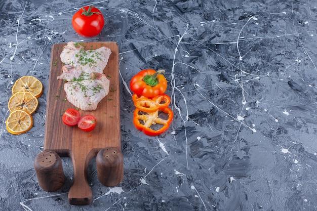 Ailes de poulet et tomates en tranches sur une planche à découper à côté d'un assortiment de légumes, sur le fond bleu.