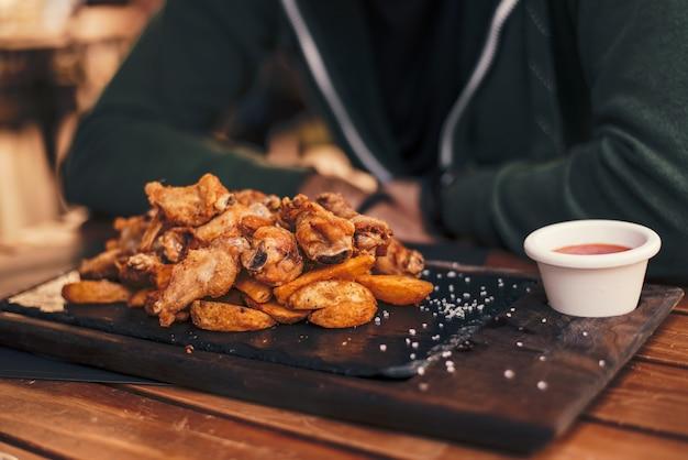 Ailes de poulet avec trempette sur une plaque de bois.