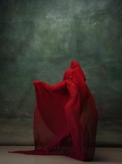 Ailes volantes. ballerine classique gracieuse dansant sur fond de studio sombre. tissu rouge foncé. le concept de grâce, d'artiste, de mouvement, d'action et de mouvement. semble en apesanteur, flexible. style de mode.