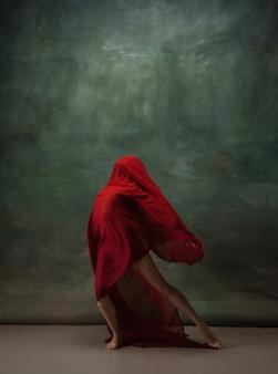 Ailes volantes gracieuse ballerine classique dansant sur fond de studio sombre tissu rouge profond