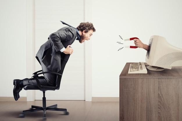 L'aimant attire un homme vers un ordinateur. capturer les gens grâce au marketing