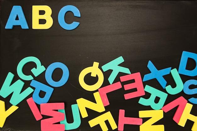 Aimants alphabet dans un pêle-mêle sur tableau noir avec abc dans l'ordre