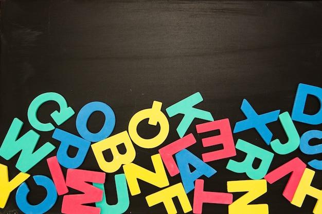 Aimants alphabet dans un pêle-mêle sur tableau noir