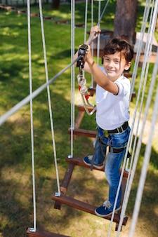 Aime les aventures. la vue de dessus d'un garçon préadolescent joyeux escalade dans un parc de cordes et souriant à la caméra tout en se déplaçant le long des sentiers