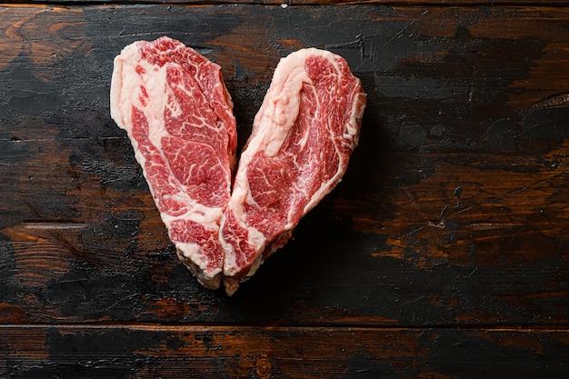 Aime le steak de boeuf bio cru sur table en bois foncé vintage
