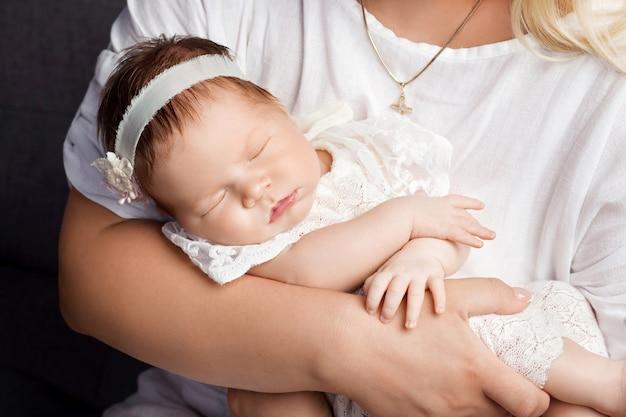Aimer babygirl dormir dans les mains de sa mère. image en gros plan. heureuse mère et sa petite fille nouveau-née smilibg qui glisse.