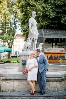 Aimer un couple d'âge moyen s'embrassant tout en se penchant en arrière sur la fontaine en pierre de la vieille ville et en profitant de leur rendez-vous et de leur promenade. beau couple d'âge mûr dans la vieille ville