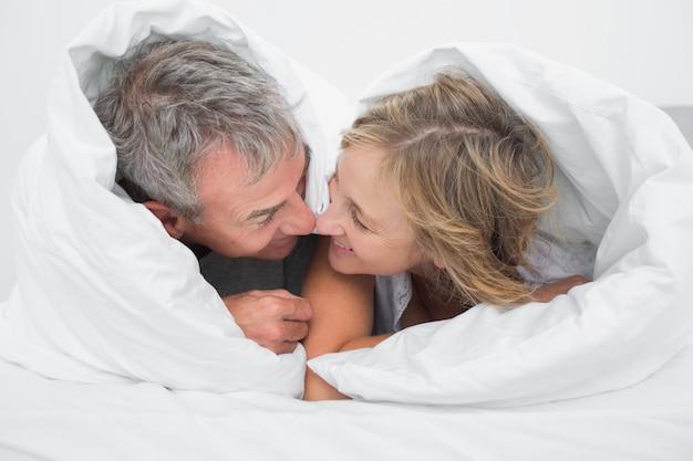 Aimer couple d'âge moyen sous la couette