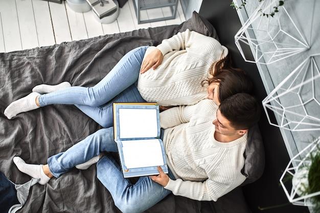 Aimer un couple enceinte, s'allonger sur le lit et se regarder. en prévision du bébé, une nouvelle vie, le bonheur et les problèmes d'une jeune famille à la naissance d'un enfant.
