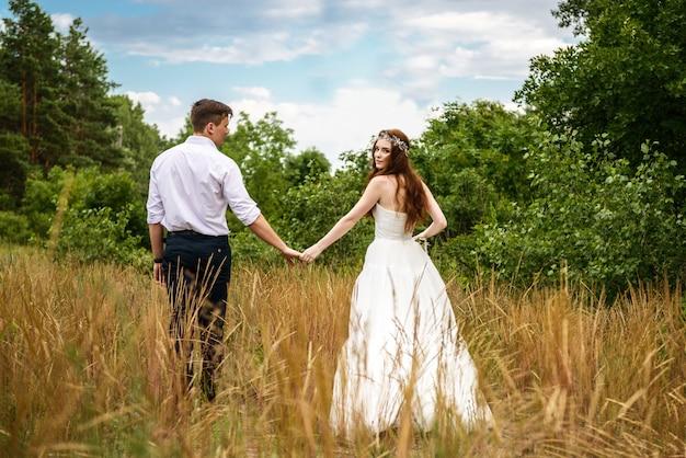Aimer Couple Mariée Et Le Marié Se Tiennent La Main Dans La Forêt Photo Premium