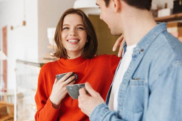 Aimer les gens femme et homme en tenue décontractée souriant et passer du temps ensemble tout en buvant du thé au café