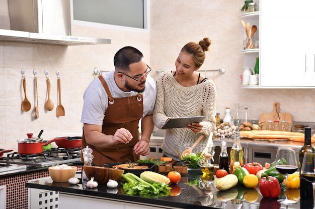 Aimer le jeune couple asiatique à l'aide de tablette numérique et cuisiner dans la cuisine faire des aliments sains ensemble se sentir amusant