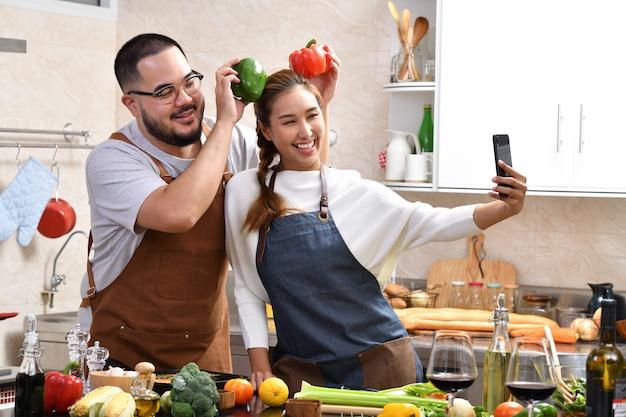 Aimer le jeune couple asiatique cuisine dans la cuisine faire des aliments sains ensemble se sentir amusant et à l'aide de smartphone pour prendre des selfies