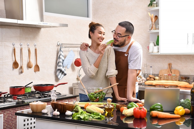 Aimer le jeune couple asiatique cuisiner dans la cuisine faire des aliments sains ensemble se sentir amusant