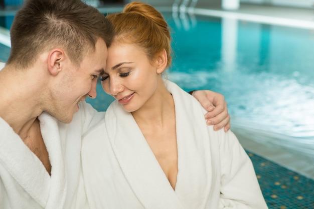 Aimer le jeune couple dans des robes en éponge se détendre au bord de la piscine ensemble