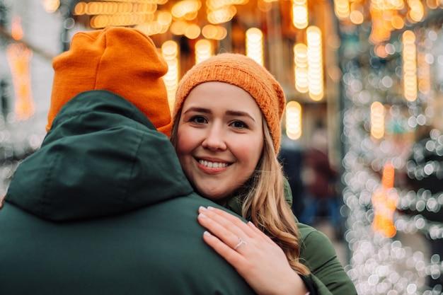 Aimer le jeune couple debout ensemble à l'extérieur entre les guirlandes à la saison d'hiver