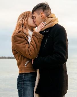 Aimer le jeune couple en hiver par la plage s'embrasser