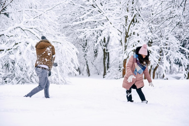 Aimer le jeune couple jouant avec des boules de neige dans un parc d'hiver
