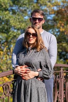Aimer le jeune couple posant sur un pont en fer forgé à l'extérieur dans un parc d'automne debout dans une étreinte étroite souriant à la caméra