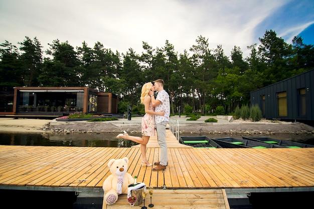 Aimer le jeune couple s'embrasse sur une jetée en bois. histoire d'amour sur la jetée