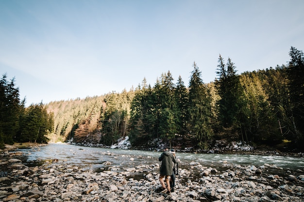 Aimer le jeune couple se promène dans la nature. la rivière avec des pierres coule entre la forêt et les montagnes. paysage.