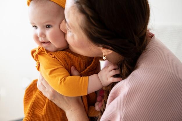 Aimer la mère de race blanche tenir le petit baiser de l'enfant en bas âge, profiter du moment à la maison ensemble, maternité, concept de garde d'enfants