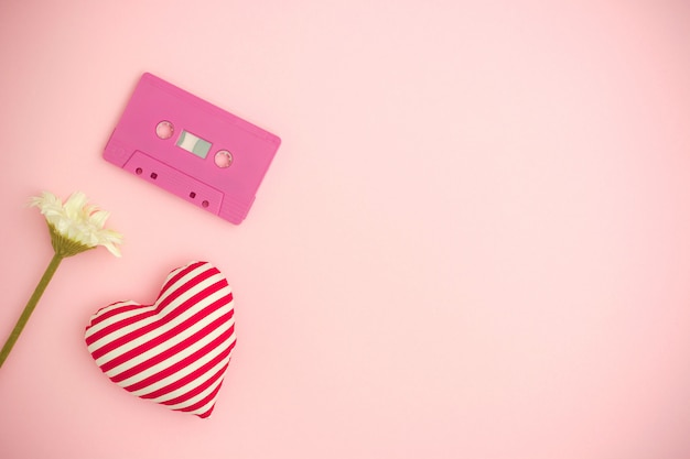 Aimer la musique. fond de saint valentin avec cassette de bande audio, une fleur et un coeur rouge.
