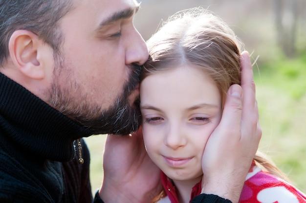 Aimer la petite fille embrassant son père heureux à l'extérieur.
