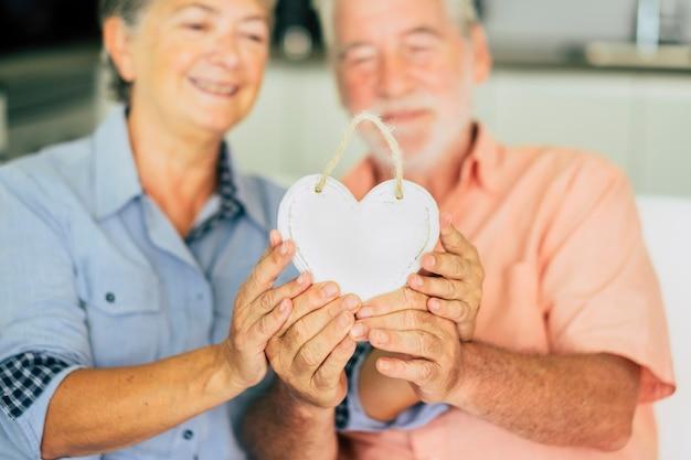 Aimez le concept de célébration de la saint-valentin avec un vieux couple de personnes âgées prenant un foyer blanc ensemble