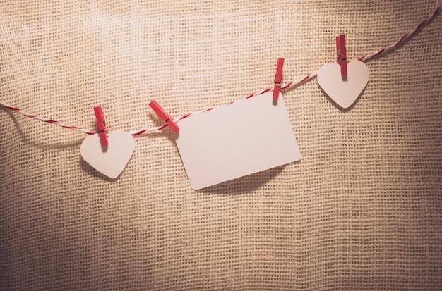 Aimez les cordons naturels et clips rouges suspendus des coeurs de la saint-valentin